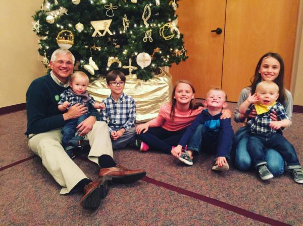 Our pastor, Dr. Steve Ayers is sitting under the Christmon Tree with his grandchildren.